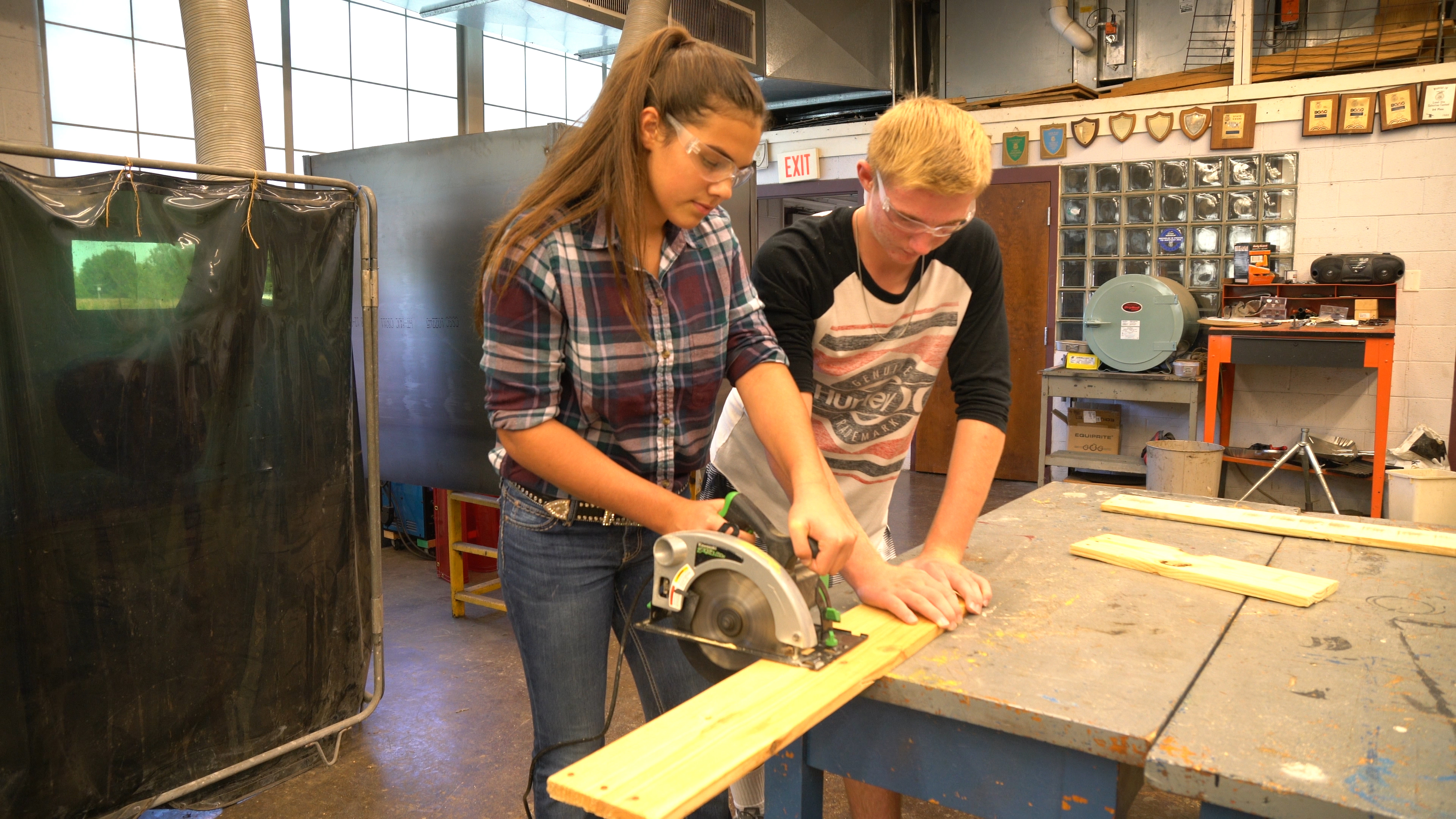 Two students using a circular saw to cut a board