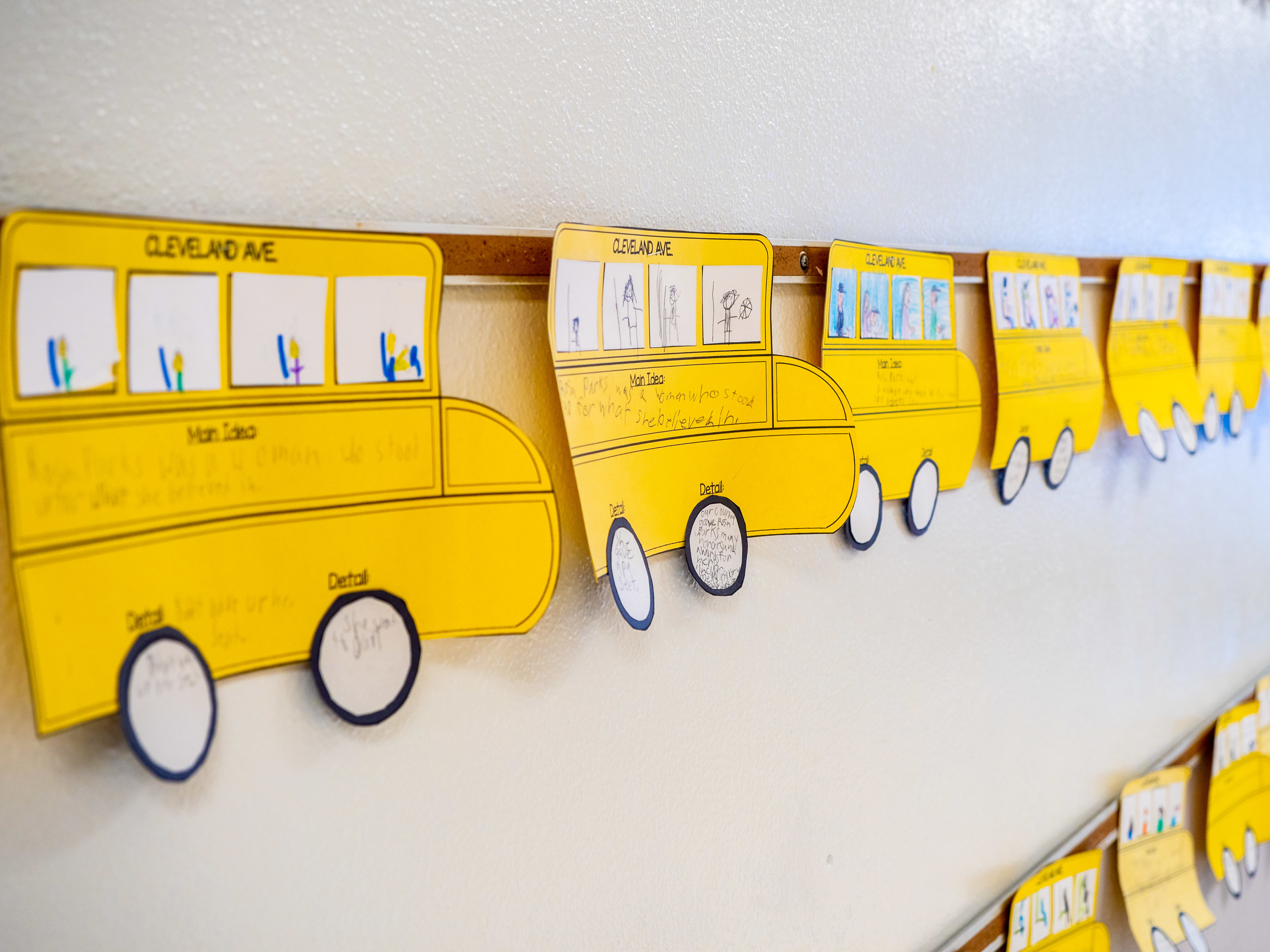 Student work hanging in the hallway in the shape of school busses